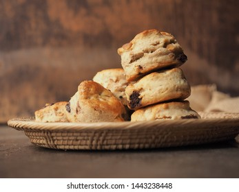 Scones with chocolate chip in basket on wood table.