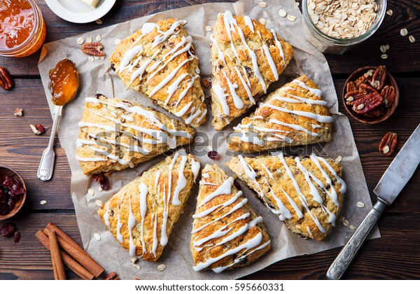 Scones with oats, cranberry and pecan nuts on wooden background. Top view