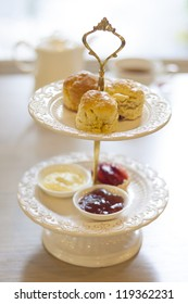 scones on two tiered tray with teapot and cup background.