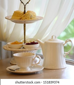 scones on two tiered tray with teapot and cup