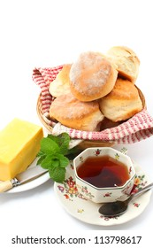 Scones with tea and butter isolated on white