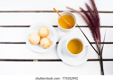 Scones, tea and fresh fruit on wooden white table.