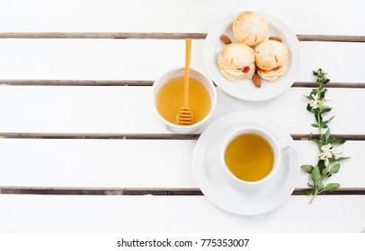 Scones and tea on wooden white table.