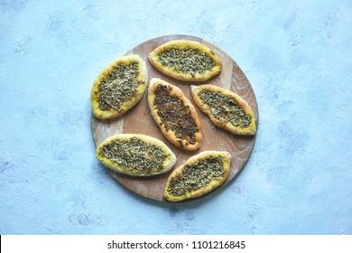 Scones with Zatar. Manakish Arabic on a wooden tray. Arabic cuisine.