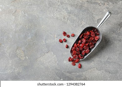 Scoop with cranberries on grey background, top view with space for text. Dried fruit as healthy snack
