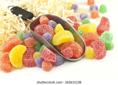 A scoop of delicious chewy assorted gumdrops on a white background with plenty of space for text, focus on front candy