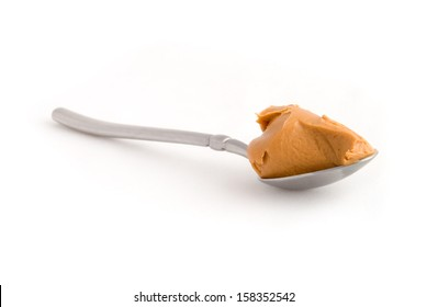 Scoop of peanut butter on a metal spoon isolated on white.