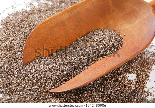 scoop and pile of healthy chia seeds on white background
