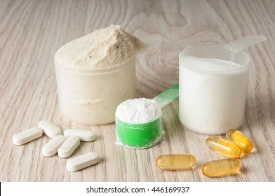 scoop of protein, bcaa and creatine, omega in pills on wooden background