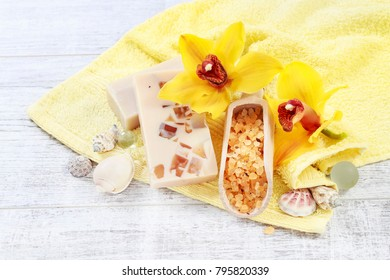Scoop of sea salt, bar of handmade soap and two yellow orchid flowers. Spa set on white wooden table.