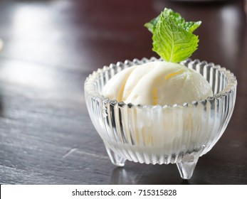 A scoop of vanilla ice cream decorated with mint leaf on top in glass bowl.