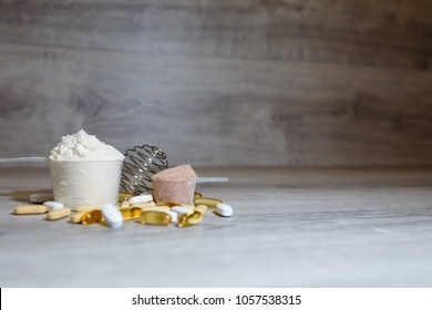 Scoop with whey protein and scoop with chocolate protein and tablets and vitamins omega 3 for sports and dietary nutrition. Complex vitamins and minerals.