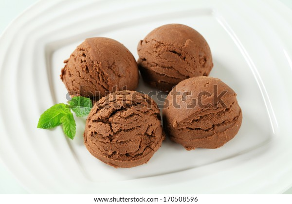 Scoops of chocolate ice cream with fresh raspberries