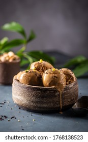 Scoops of coffee or chocolate ice cream in a bowl with green leaves on dark background