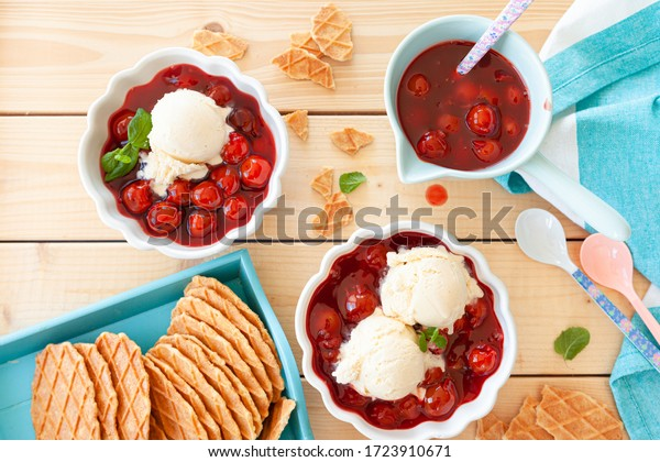 Scoops of vanilla ice cream with cherries and crunchy waffles
