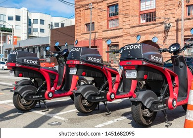 Scoot Rides electric rideshare zero emissions scooters wait for riders on the street. Scoot Networks was acquired by Bird - San Francisco, California, USA - July 12, 2019