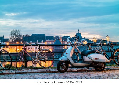 Scooter and bicycles in front of the Dutch river Maas in Maastricht