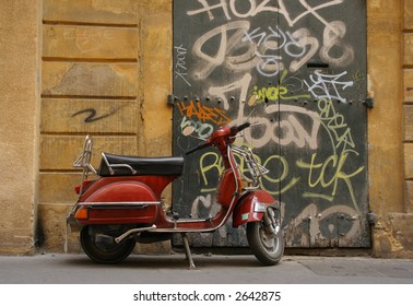 a scooter parked in front of a graphitti sprayed doorway in aix en provence south of france europe