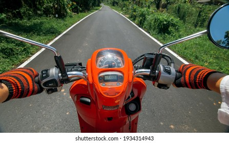 Scooter road trip. POV view, first person. Men on red motorbike in white clothes on drive forest road trail. Hold the steering wheel motorbike. Motorcycle rent. Asia Thailand transport.