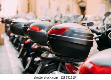 Scooters With Removable Trunks. Many Motorbikes, Motorcycles, Scooters Parked In Row In City Street. Close Up Trunk Or Top-box Is A Storage Compartment Fitted Behind The Seat