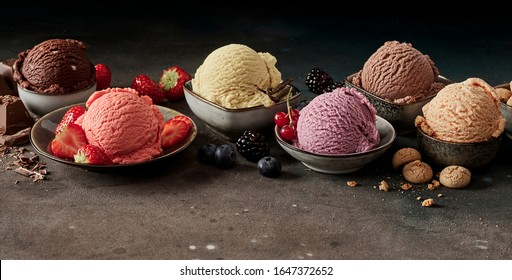 Scopes of various flavour ice cream in small bowls, served with berries and other ingredients, viewed in close-up on dark table. Professional studio shot