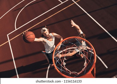 Score! Top view of young man in sports clothing scoring a slam dunk while playing basketball outdoors