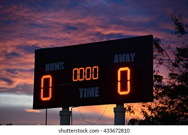 scoreboard with home and guests written on it at sunset time.