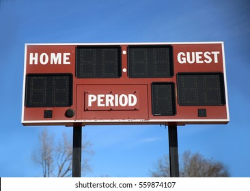 a scoreboard with home and guests written on it in front of a blue sky on a sunny summer day