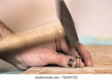 Scoring a nail with a hammer, a trauma on the construction, a hammer blow on the finger