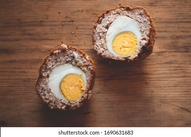 Scotch egg cut in half on wooden background