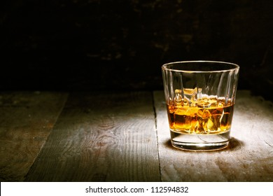 Scotch on wooden background with copyspace. An old and vintage countertop with highlight and a glass of hard liquor