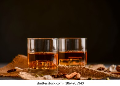 Scotch on wooden background with copyspace. Whiskey in shot glasses. Black background. Whiskey with cinammon and other spices.