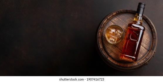 Scotch whiskey bottle, glass and old wooden barrel. With copy space. Top view flat lay