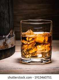 Scotch whiskey, rum, or bourbon. Glass of whiskey with ice cubes sits on a wooden table next to a wooden whiskey barrel in the basement of a wine cellar.