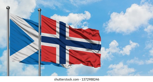 Scotland and Norway flag waving in the wind against white cloudy blue sky together. Diplomacy concept, international relations.