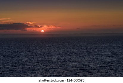 Scotland on the horizon as the sun sets on the North Sea.