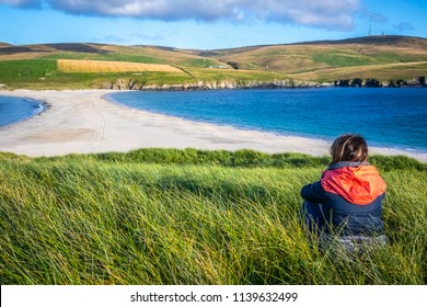 Scotland, Shetland Islands, Young woman at St Ninian's Beach, A tombolo is a deposition landform in which an island is attached to the mainland by a narrow piece of land such as a spit or bar.