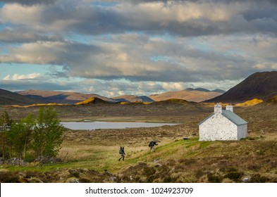 SCOTLAND, UNITED KINGDOM - MAY 18, 2017: Hiker approching mountain shelter, the Cape Wrath Trail , Scottish Highlands.