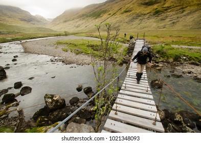 SCOTLAND, UNITED KINGDOM - MAY, 2017 : Trekker on the Cape Wrath Trail, crossing a stream. near Camusrory village.