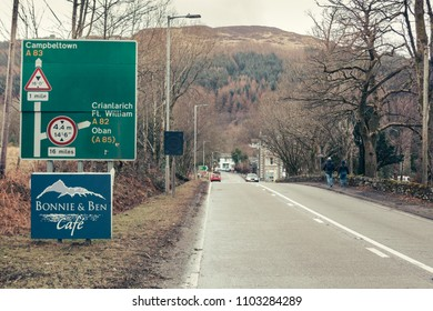 Scotland/UK-03.17.2018: Route A83 towards Campbeltown, passing through the Tarbet village near Loch Lomond in Scotland, road scheme sign on the left, couple walking along the right side of the road