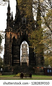 Scott Monument on Edinburgh's Princess Street, a Victorian Gothic monument to Scottish author Sir Walter Scott with clocktower at the center and bench with two people at in the foreground.