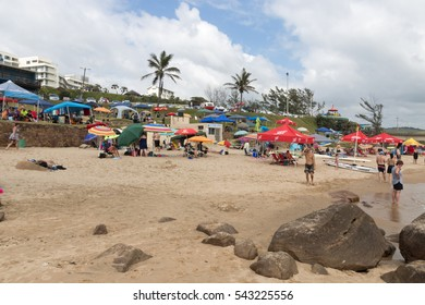 SCOTTBURGH, DURBAN, SOUTH AFRICA - DECEMBER 23, 2016: Many unknown people and colorful umbrellas on early morning  beach at Scottburgh south of Durban in South Africa