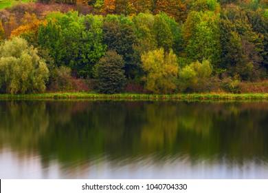 Scottish autumn scene of greenwood forest reflecting on calm lake surface.