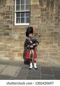 Scottish bagpiper dressed in kilt, traditional red and black tartan dress. Edinburgh, Scotland, May 2014