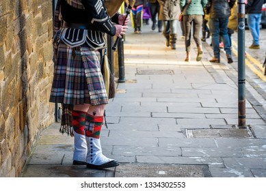 Scottish bagpiper dressed in traditional red and black tartan dress playing bagpipe on the Royal Mile.