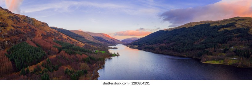 Scottish beautiful colorful sunset landscape with Loch Voil, mountains and forest at Loch Lomond & The Trossachs National Park. Nature evening scenery in Scotland over the mountain lake.