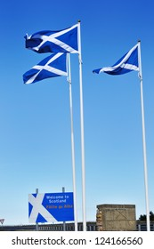 The Scottish border with England with Welcome to Scotland sign and Saltire flags.