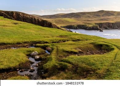 Scottish burn, or stream, flowing towards cliffs in a dramatic coastal landscpae, near Westerwick, West Mainland, Shetland, Scotland, Great Britain