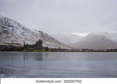 "The scottish castle ""Kilchurn Castle"" in a winter landscape with snow and a sea."