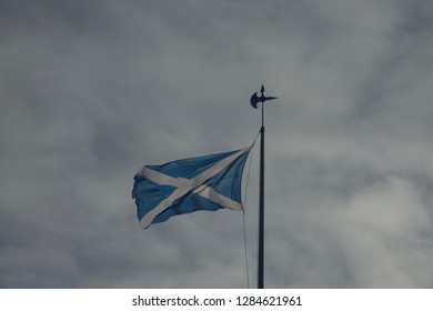 The Scottish flag, the Saltire, on a flagpole against a marbled grey cloudy sky.